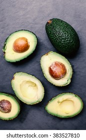 Avocado on a black background, top view image. Halved avocado, close up with copy space