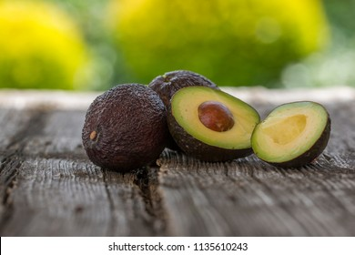 Avocado on old wooden table. Fruits healthy food concept.