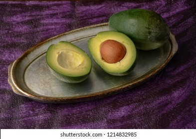 Avocado on purple table.Halfs on vintage  bowl. Fruits healthy food concept on purple background