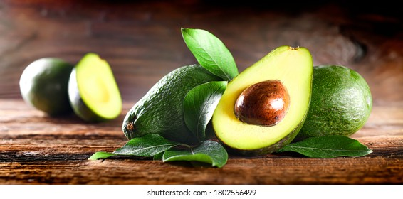 Avocado on rustic wooden table. Raw Fruits healthy green food. Avocados wide banner or panorama concept
