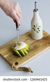 avocado on tost with egg, smorebrod, wooden cutting Board, hand