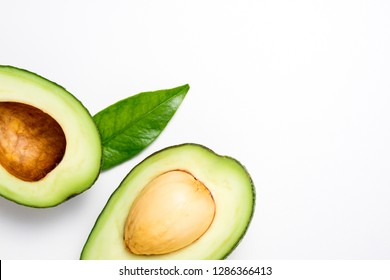 Avocado on white background. Tropical abstract background with avocado and leaf. Flat lay. Top view, copy space