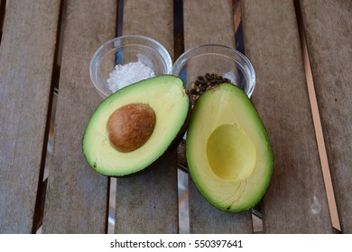 Avocado on a wooden table with salt and pepper grains