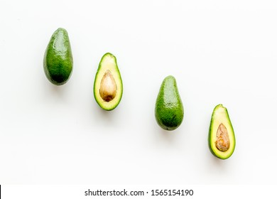 Avocado pattern - halfs of fruit - on white background top view copy space