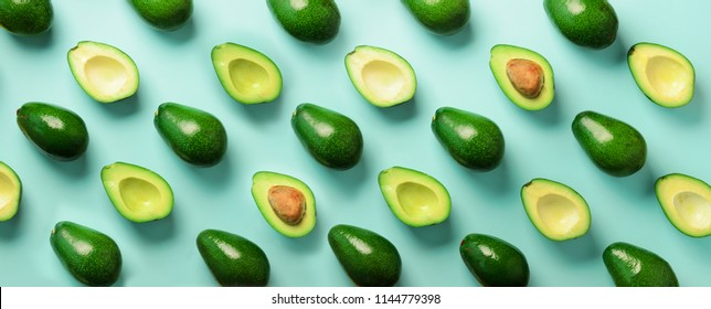 Avocado pattern on blue background. Top view. Banner. Pop art design, creative summer food concept. Green avocadoes, minimal flat lay style. Banner.