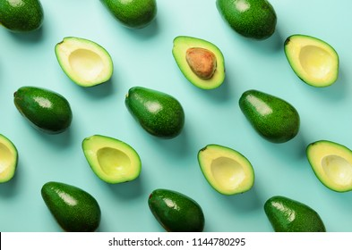 Avocado pattern on blue background. Top view. Banner. Pop art design, creative summer food concept. Green avocadoes, minimal flat lay style