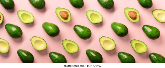 Avocado pattern on pink background. Top view. Banner. Pop art design, creative summer food concept. Green avocadoes, minimal flat lay style. Banner.