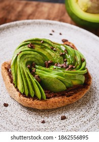 avocado rose is toast topped with sliced avocados shaped like rose, sprinkle with cacao nibs for texture, perfect for healthy breakfast