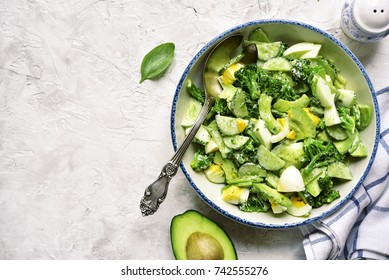 Avocado salad with broccoli,cucumber and boiled eggs in a white vintage bowl over light slate,stone or concrete background.Top view.