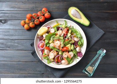 Avocado salad with shrimps, cherry tomatoes, arugula beet leaves, red onion, yellow sweet pepper. Healthy lunch plate  with vegetables and shrimps
