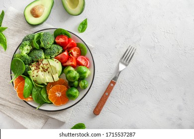 Avocado salad with tomatoes, Brussels sprouts, broccoli, spinach leaves and orange slices in plate on white background.