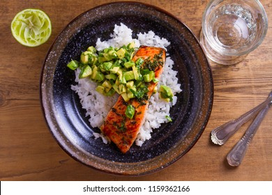 Avocado salmon rice bowl. Salmon fillet roasted in honey, lime, cilantro glaze and fresh cilantro avocado. Fish steak. View from above, top studio shot