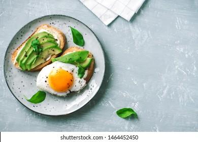 Sandwich à l'Avocado avec Oeuf frit - avocat tranché et oeuf sur pain grillé avec de l'arugula pour un petit-déjeuner sain ou un en-cas.