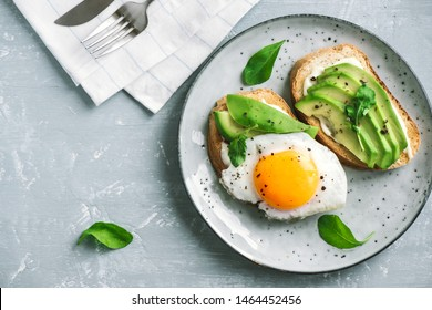 Avocado Sandwich with Fried Egg - sliced avocado and  egg on toasted bread with arugula for healthy breakfast or snack.