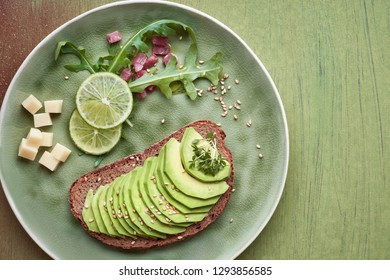 Avocado sandwich and green salad with ham cubes on brown-green textured background, top view