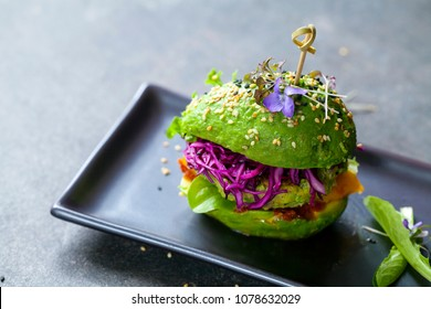 Avocado sandwich with green vegan burger,  roast yellow pepper and pickled red cabbage