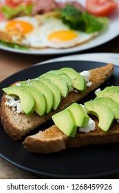 Avocado sandwich on dark toast bread made with fresh sliced avocado, cream cheese.