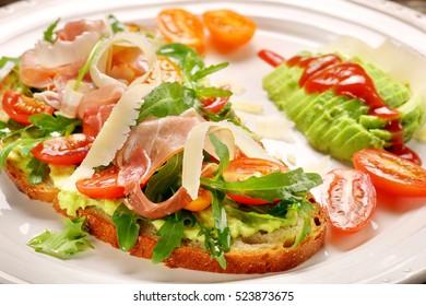 Avocado sandwich on fresh bread with arugula ham tomato and cheese