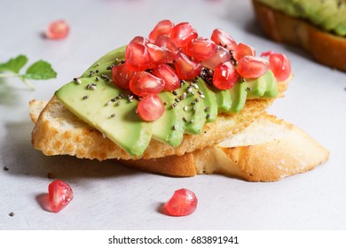 Avocado sandwich on sliced  bread toast made with fresh sliced avocados and pomegranate seeds.