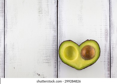 Avocado in the shape of a heart on a rustic white table