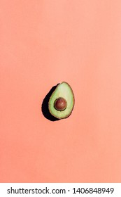 Avocado shot from above, cut in half, placed in the middle of a light skin colored background