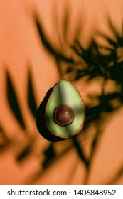 Avocado shot from above, cut in half, placed in the middle of a orange colored background, with palm leaf shadows over it.