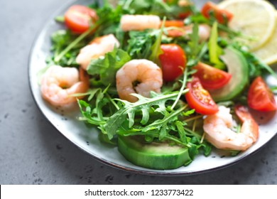 Avocado Shrimp Arugula Salad on grey stone background, copy space. Healthy balanced food, diet green salad with Shrimps (prawns), avocado and arugula.