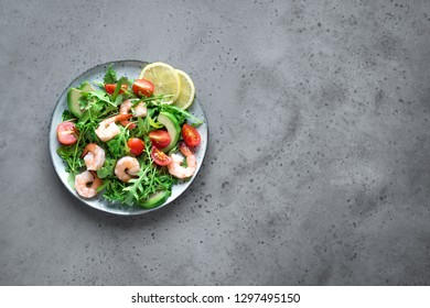 Avocado Shrimp Salad with Arugula and Tomatoes on grey stone background, copy space. Healthy diet green salad with Shrimps (prawns), avocado, cherry tomato and arugula.