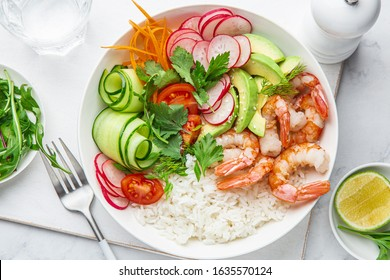 Avocado, shrimps, cucumber, tomato, radish, carrot and rice salad bowl. Healthy food.  White background, top view