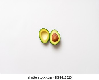 Avocado sliced with seed isolated in white background viewed from above - flatlay look