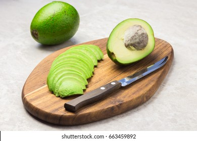 Avocado slices and knife on wooden board. cooking avocado salad.