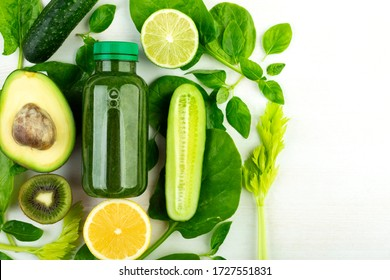 Avocado, spinach, cucumber, kiwi, lime, lemon, celery, spinach - green vegetables laid out around a bottle of green detox drink.