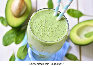 Avocado and spinach green smoothie on a light wooden table.