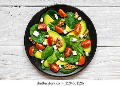 avocado and spinach salad with tomatoes cherry, feta cheese and walnuts in a plate on rustic wooden table. top view. healthy food