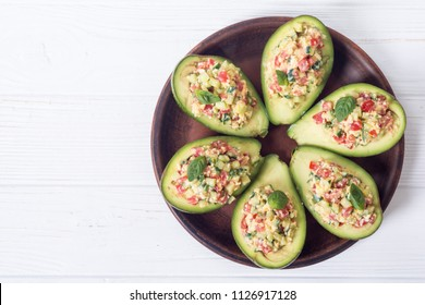 Avocado stuffed with cucumber , tomatoes , eggs and basil . Healthy food