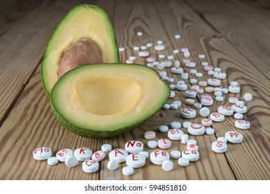 Avocado and synthetic vitamins on a wooden table. The concept of healthy food and natural vitamins. Healthy lifestyle.