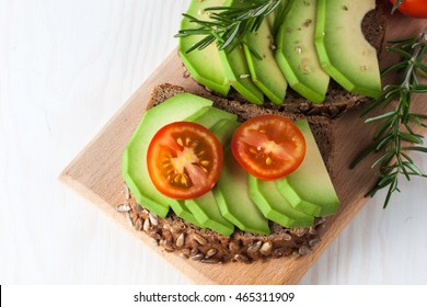 Avocado toast, cherry tomato on wooden background. Breakfast with toast avocado, vegetarian food, healthy diet concept.