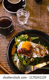 Avocado toast with egg and pomegrate seeds on black plate at restaurant table. Dark food photography concept. Copy space
