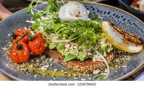 Avocado Toast featuring smashed avocado, truss tomatoes, boiled egg on sourdough toast