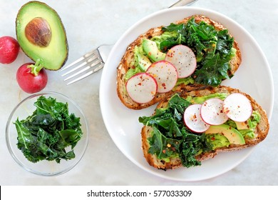 Avocado toast with kale and radish on whole grain bread, overhead scene on marble
