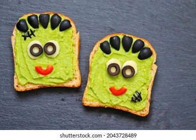 Avocado toast look like Green Monster for Halloween made from toast, mashed avocado, black olives, mozzarella sheet and red bell peppers on slate plate. Art food idea for kids party. Top view