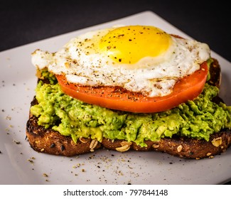 Avocado toast on white plate made with whole grain bread, sunny side up fired egg, and a sliced tomato.