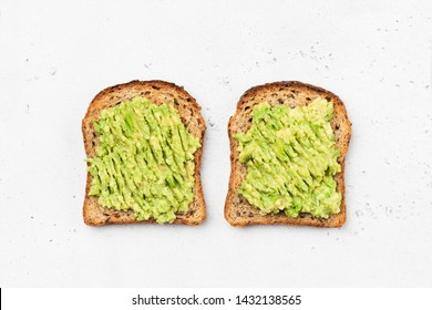 Avocado toast on whole grain sandwich bread. Table top view. Mashed avocado toasts. Concept of healthy eating, dieting, vegan vegetarian food