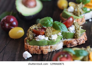 Avocado toast sandwich with avocados, pesto, feta cheese, fresh from the garden basil and heirloom tomatoes, over a rustic wooden background. Greek food and healthy vegetarian diet concept.