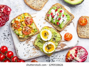 Avocado toasts with egg, tomatoes, seasonings on white wooden rustic cutting board, stone background. Ingredients for healthy breakfast avocado sandwiches with different toppings, top view, close-up