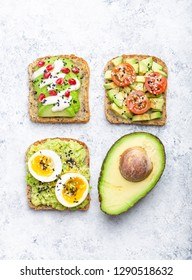 Avocado toasts with egg, tomatoes, seasonings and a half of whole avocado over white stone background. Healthy breakfast avocado sandwiches with different toppings, top view, close-up