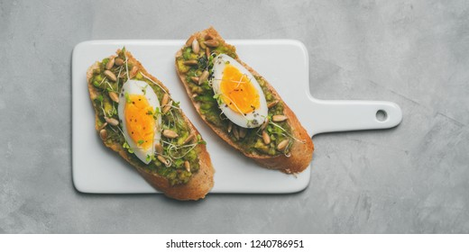 Avocado toasts with eggs, fresh mini herbs, sunflower seeds on a ceramic white board over grey concrete background, top view, long wide banner background copy space. Diet food concept, gluten-free.