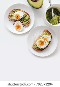 Avocado toasts with hard boiled eggs, preparing healthy breakfast, top view with copy space