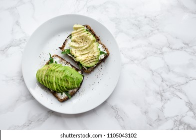Avocado toasts on rye bread with sliced avocado, arugula, creme cheese with salt and pepper for healthy breakfast on light marble background. Vegetarian food. Clean eating. Top view. Copy space.