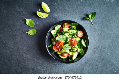 Avocado, tomato and cucumber salad with fresh herbs on dark stone background. Healthy summertime salad. Copy space